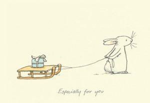 Carte de voeux avec texte en anglais représentant un lapin blanc dans la neige tirant une luge en bois avec un cadeau
